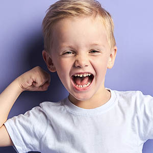 boy smiling with curled arm, pediatric dentistry baytown tx