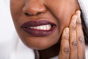 woman wincing from teeth grinding